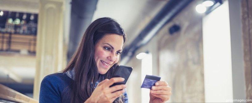 девушка держит телефон и банковскую карту в руках