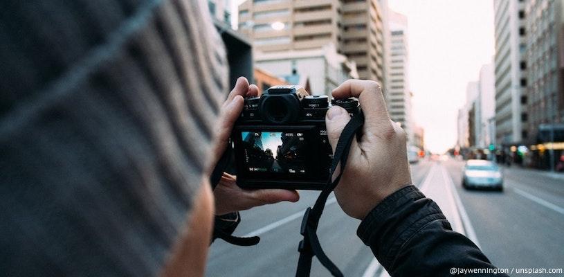 мужчина фотографирует городскую улицу