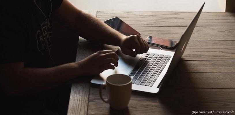 мужчина сидит перед ноутбуком с чашкой