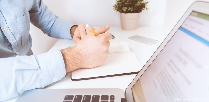 мужчина пишет текст в блокнот перед компьютером