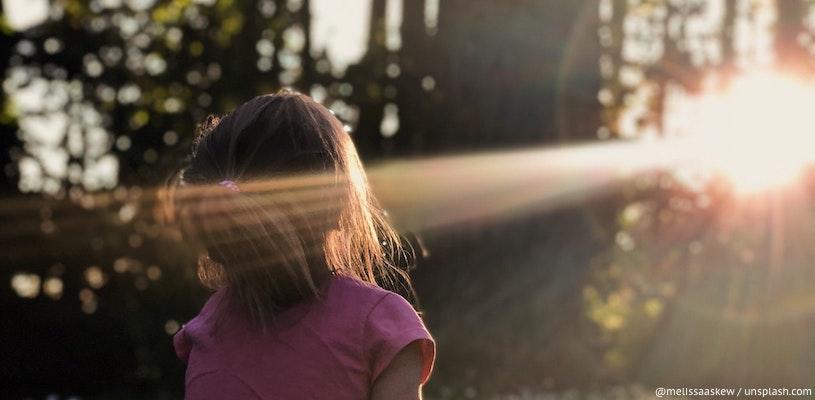 девочка смотрит на луч солнца в лесу