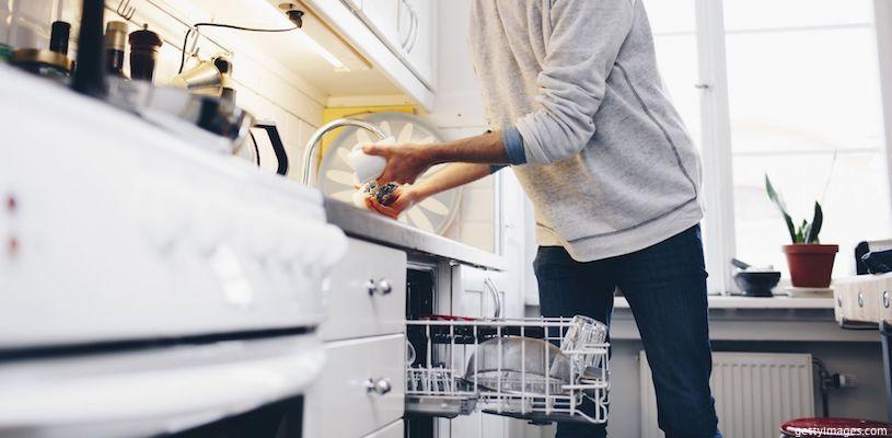 мужчина загружает посуду в посудомойку