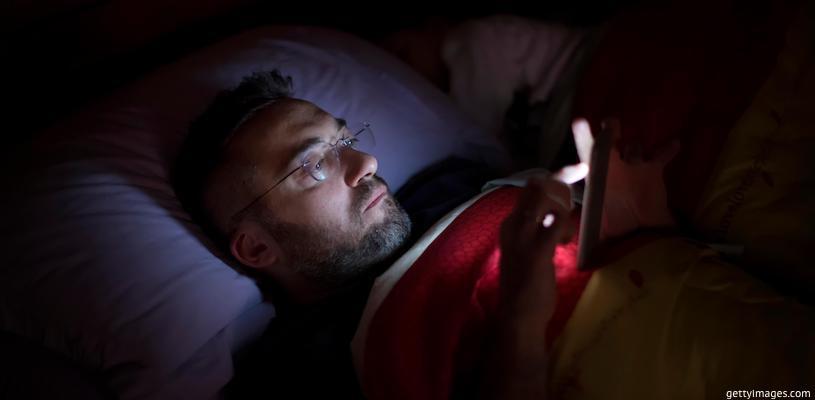 мужчина смотрит в телефон перед сном