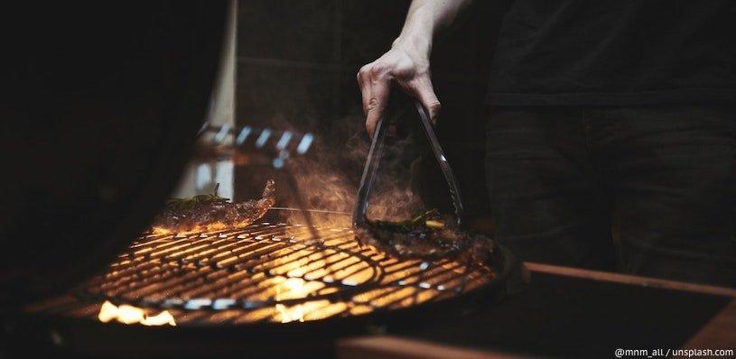 мужчина жарит мясо на гриле