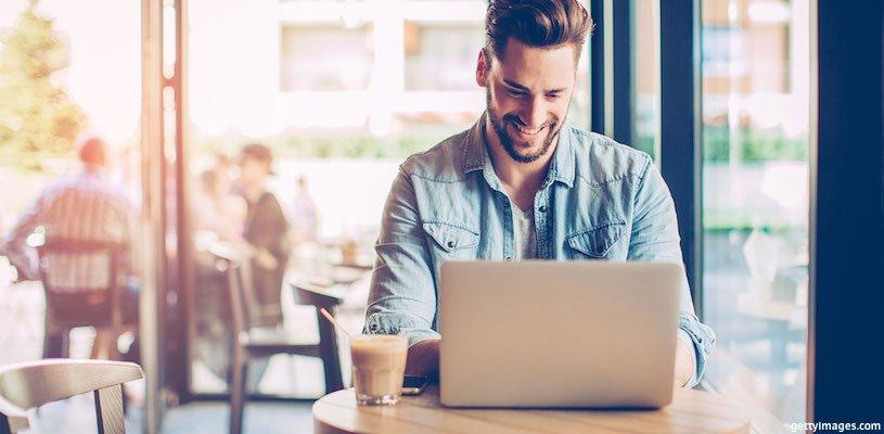 молодой человек работает с ноутбуком в кафе