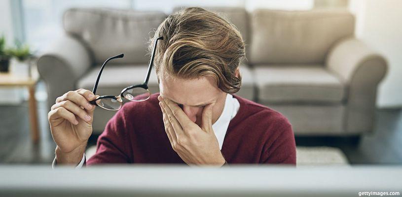 мужчина протирает глаза перед компьютером