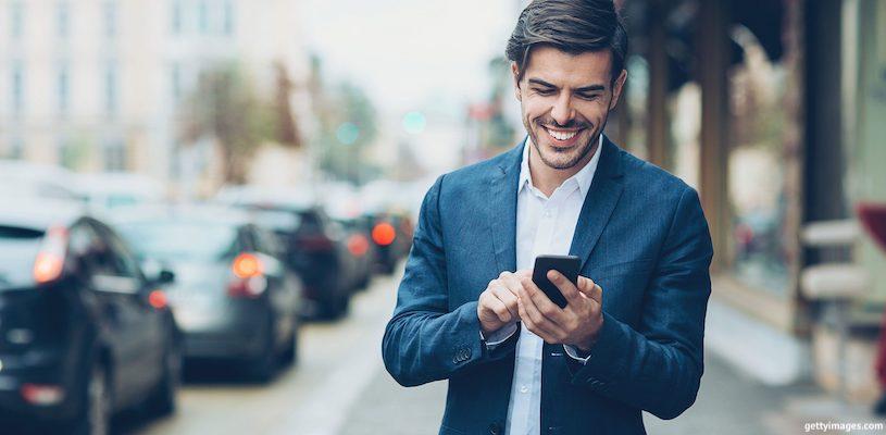 молодой предприниматель смотри в телефон и улыбается
