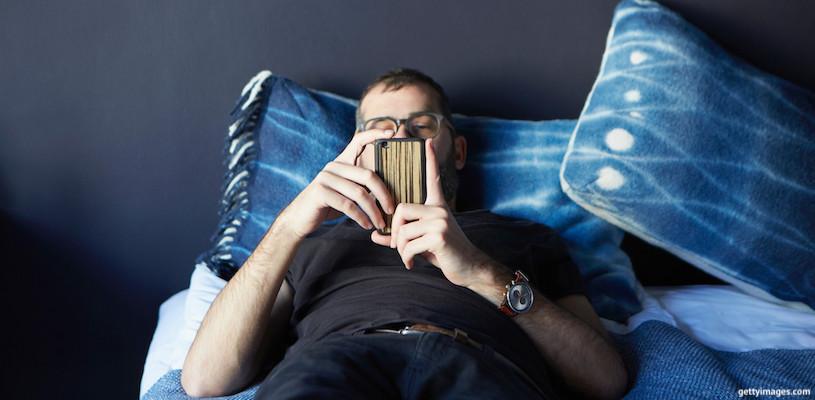 мужчина лежит на кровати и смотрит в смартфон