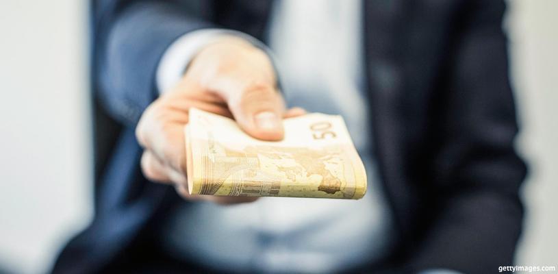 мужчина отдает пачку денег
