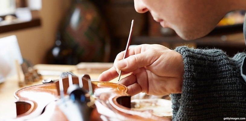 мужчина реставрирует скрипку