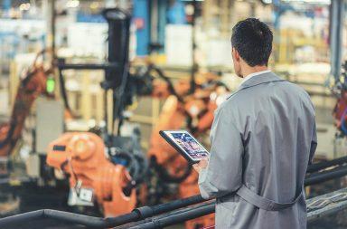 мужчина следит за работой завода с планшета