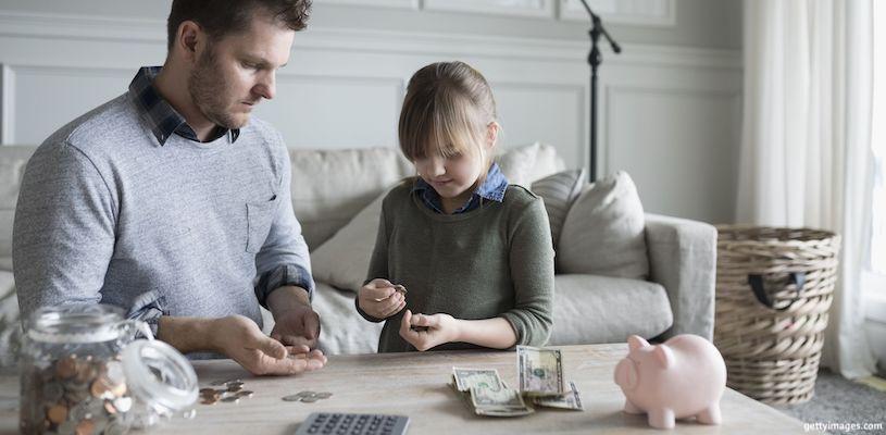 папа с дочкой складывают деньги в копилку