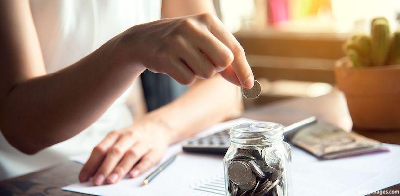женщина бросает монетку в банку
