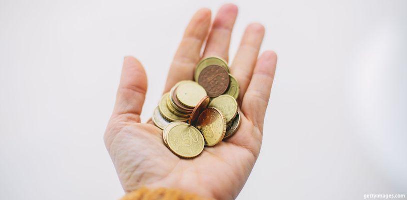 женщина держит в руке монеты