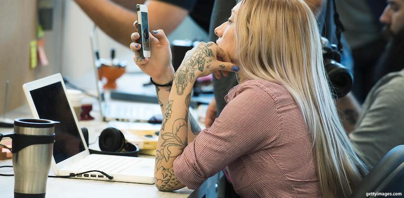 женщина сидит в телефоне на работе