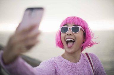 девушка с розовыми волосами делает селфи