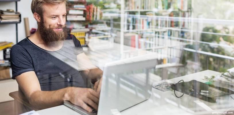 молодой мужчина с бородой сидит перед монитором
