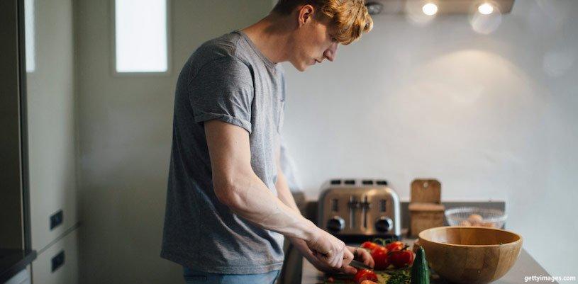 молодой парень режет салат на кухне