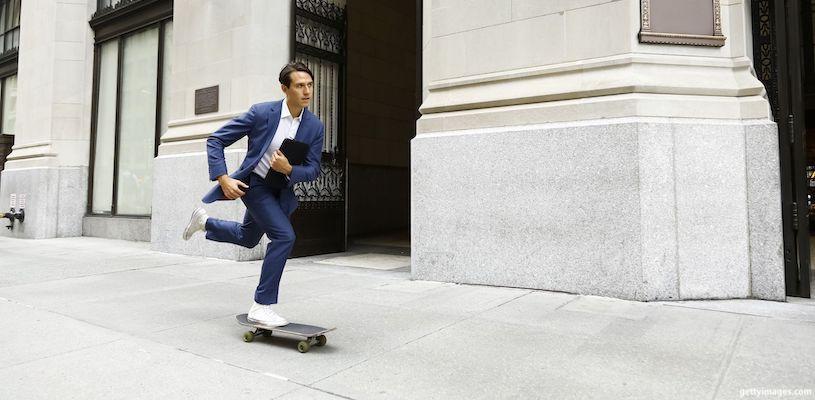 парень едет на скейте на работу