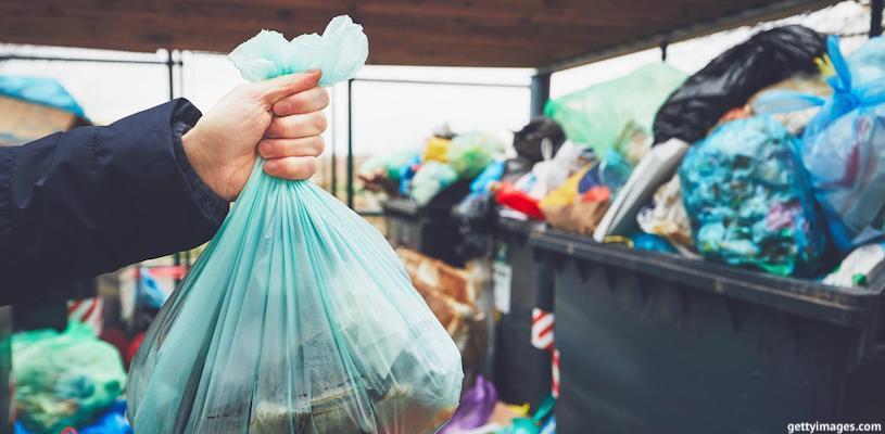 человек выбрасывает мусор в контейнер