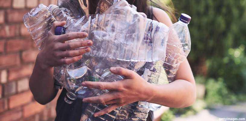 девушка несёт пластиковые бутылки
