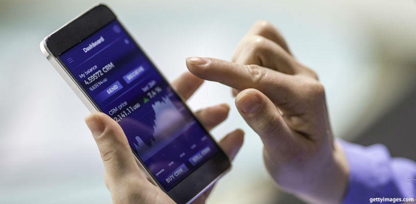 мужчина инвестирует на мобильном телефоне