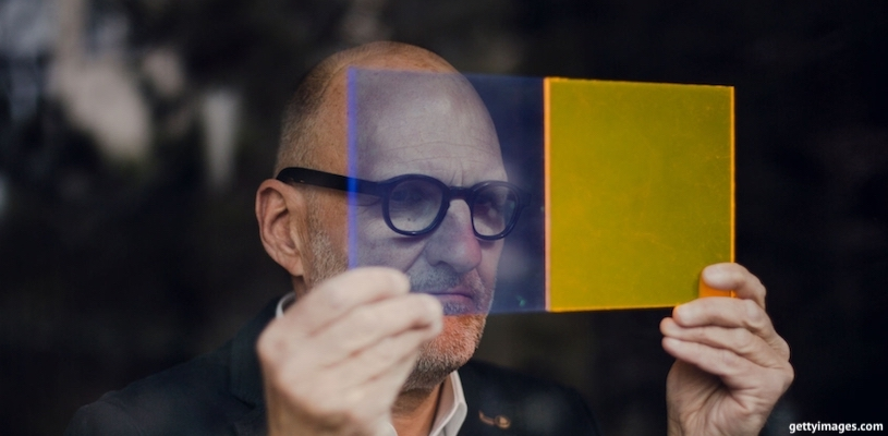 мужчина смотрит на разноцветные стёкла