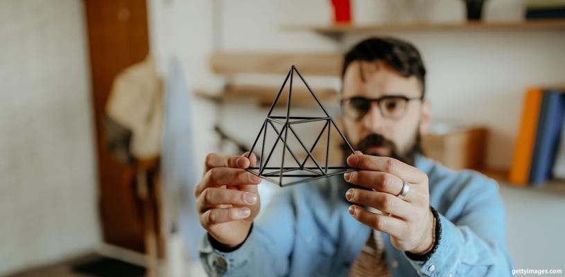 мужчина смотрит на пирамиду