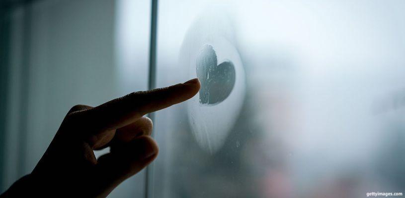 рисует сердечко на стекле