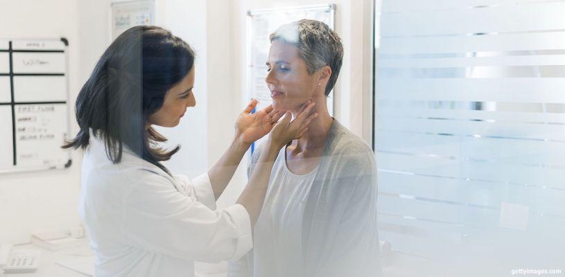 врач осматривает щитовидную железу