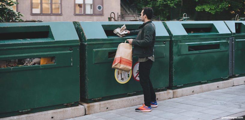 мужчина выбрасывает сортированный мусор